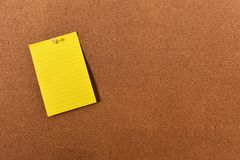 Sticky Note and Corkboard. An image of a bright sticky note pinned to a wooden cork-board stock photo