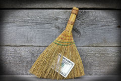 Image of broom with dollars, close-up. Image of broom sweeping dollars on wooden floor, close-up Stock Images