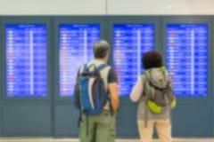 Image brouillée de passager regardant des écrans d'horaire dans l'aéroport Images libres de droits