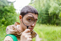 Image of brunet biologist with magnifying glass Royalty Free Stock Images
