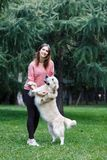 Image of brunette holding dog by front paws on green lawn Royalty Free Stock Images