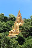 Image of Buddha. On green mountain and blue sky behind stock photo