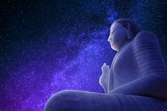 Image of Buddha meditating. With the universe full of stars in the background stock photos