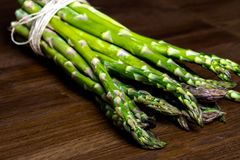 Green Asparagus with cups of green herbs on a black background Stock Images