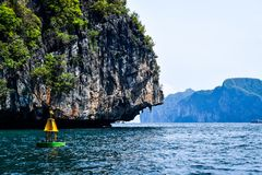A  buoy in front of a rock with vegetation. Image of a buoy in the Andaman sea in front of a rock formation Royalty Free Stock Images
