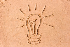 Image of a burning bulb in sand Stock Photography