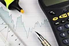 An image of a business concept with calculator and pen. Abstract Stock Image
