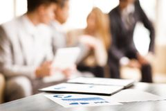 Image of business documents. With working team communicating at background Stock Image