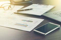 Image of business documents on workplace with analysis chart,graph business summary report, laptop and smartphone on the office t royalty free stock photography