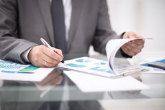 Image of business documents on workplace with partners interacting. On background Royalty Free Stock Photography