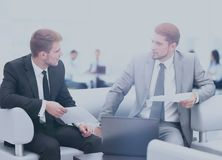 Business people Having Meeting Around Table In Modern Office. Image of business partners discussing documents and ideas at meeting Royalty Free Stock Photos