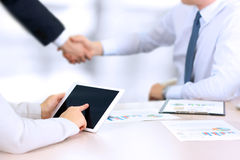 Image of business partners handshaking over business objects on workplace. businesswoman working with digital tablet Stock Images