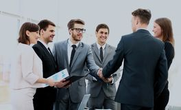 Image of business partners handshaking after signing contract.