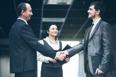 The image of a business team discussing latest financial results fixing the deal with a handshake. The image of a business team discussing latest financial Royalty Free Stock Images
