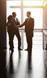 The image of a business team discussing the latest financial results and fixing the deal with a handshake. The image of a business team discussing latest Royalty Free Stock Image