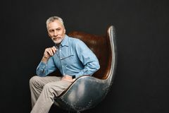 Image of businesslike gentleman 50s with grey hair and beard in. Glasses sitting on wooden armchair with meaningful look isolated over black background Stock Images