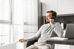 Image of businesslike man 30s wearing casual clothing working on. Laptop while looking out window and speaking on cell phone at home stock photography