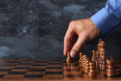 Image of businessman hand moving chess figure over chess board. Business, competition, strategy, leadership and success concept. Stock Image