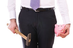 Businessman with piggy bank and hammer. Royalty Free Stock Photos