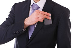 Businessman putting cellphone into pocket. Royalty Free Stock Image
