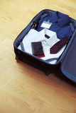 Image of businessman's clothes in travel bag Stock Images