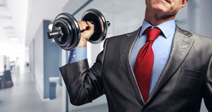 Image of businessman in suit raising dumbbell. Tax burden concep Royalty Free Stock Photos