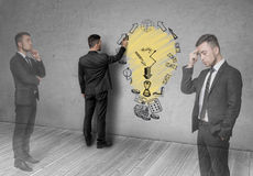 Image of businessman, thinking about how to make a profit. Image of a businessman, thinking about how to make a profit. The sketch on the wall. Process of royalty free stock image