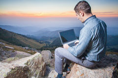 Image of a businessman on the top of the mountain, using a laptop Stock Images