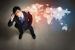 Image of businessman top view. Top view of young businessman making decision against global network back Royalty Free Stock Photo