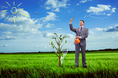 Image of businessman watering money tree Stock Images