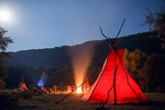 Image of camping with red tipi and people near bonfire on dark forest background. beautiful lanscape background. stock photo