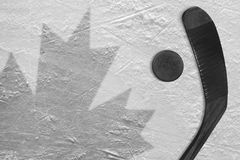The image of the Canadian flag and hockey puck with the stick Royalty Free Stock Photos