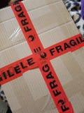 Fragile. Image of cardboard box with orange fragile tape stuck on it stock images