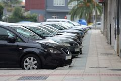 Cars parked in a row on a city street Royalty Free Stock Image