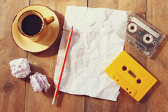 Image of cassette tape over wooden table empty crumpled paper. top view. retro filter Royalty Free Stock Photos