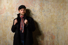 Image of a caucasian man with grungy blond hair dressed warmly in a stylish black trench coat and a funky hat and scarf for the co Royalty Free Stock Photography