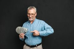 Image of caucasian middle aged man 60s with gray hair pointing f. Inger on money prize holding lots of dollar banknotes isolated over black background Stock Images
