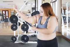 Caucasian obese woman measuring her bicep. Image of Caucasian obese woman measuring her bicep by using a measuring tape Stock Photo