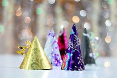 Celebrating New Years with colorful party hats. Image of Celebrating New Years with colorful party hats on twinkle light background stock photos