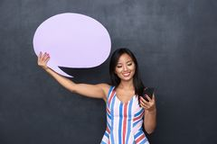 Image of charming asian woman 30s holding blank thought bubble and smartphone standing isolated royalty free stock photography
