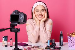 Image of charming young brunette woman advertises new beauty products, makes video her blog. Beauty vlogger sits smilling in front. Of camera with happy facial stock image