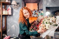 Cheeful young florist standing next to bouquets of vernal flowers in shop. Image of cheeful young florist standing next to bouquets of vernal flowers in shop stock images
