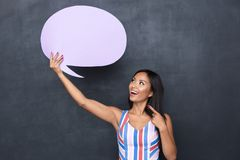 Image of cheerful asian woman 30s holding blank thought bubble above her head with copyspace for your text standing isolated over stock image