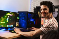 Image of cheerful gamer man playing video games on computer, wea. Image of cheerful gamer man playing video games on computer wearing headphones and using stock photo