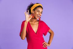 Image of cheerful happy woman 20s in hair band smiling and showing ok sign, isolated over violet background stock photography