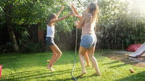 Image of cheerful laughing girls in wet clothes dancing in the garden and holding water hose. Family playing and having. Photo of cheerful laughing girls in wet royalty free stock image