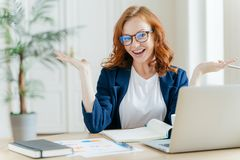 Image of cheerful redhead businesswoman watches webinar or tutorial video, uses free internet connection, raises palms with royalty free stock photos