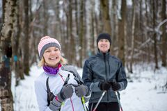 Image of cheerful sports woman and man skiing in winter forest royalty free stock image