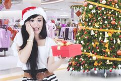 Cheerful woman getting a Christmas gift. Image of cheerful woman getting a Christmas gift while wearing Santa hat in the shopping center Royalty Free Stock Photo