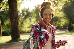Cheerful young african woman walking chatting by phone. Image of cheerful young african woman walking outdoors in park. Looking camera listening music while Stock Photography